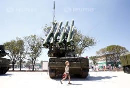 A boy walks past the Russian Buk-1M missile system at the Air defense battle masters competition as part of the International Army Games 2015 in the port town of Yeysk, Russia, August 9, 2015. REUTERS/Maxim Zmeyev